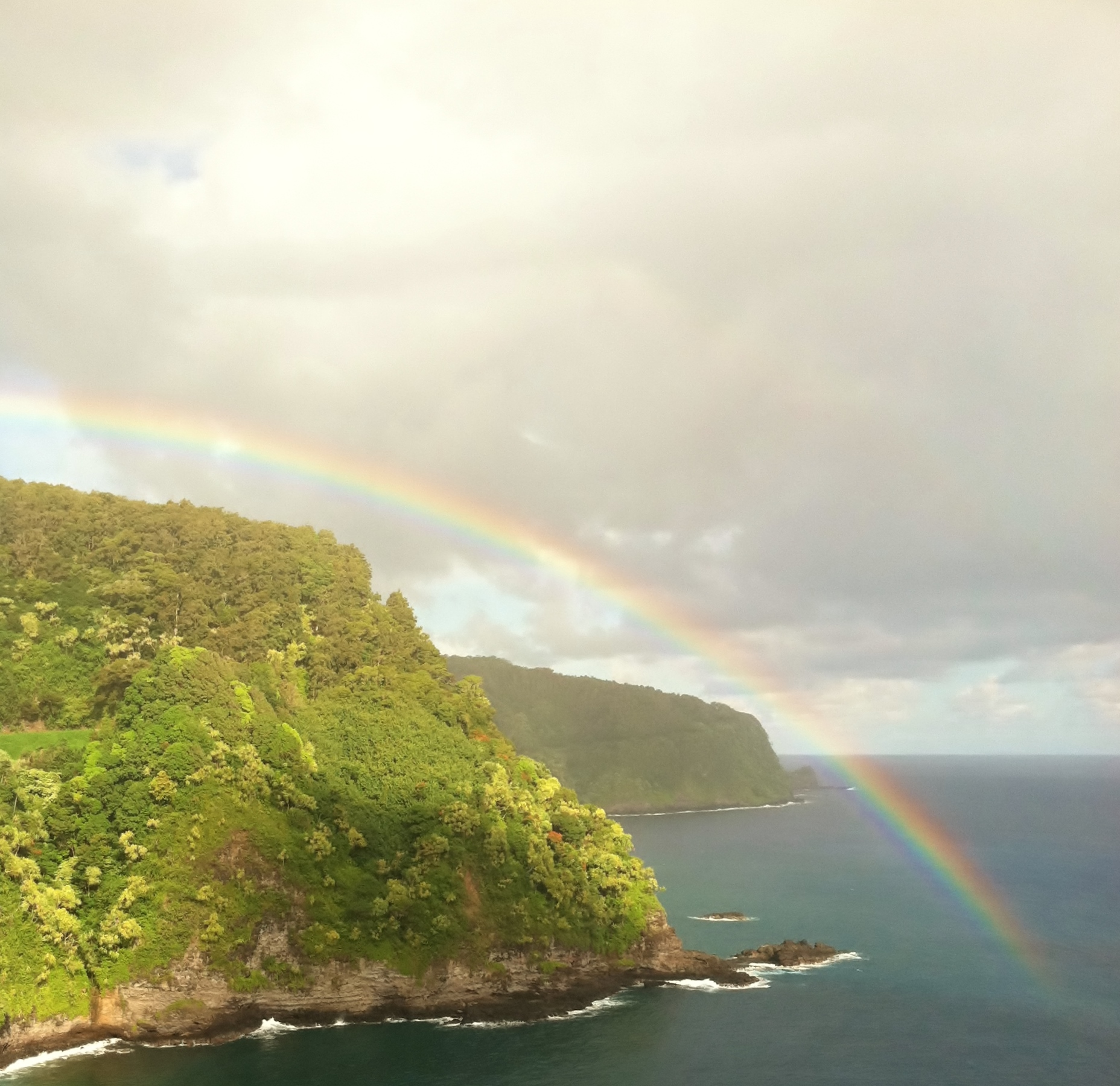 A rainbow extends over a cliff and into the calm, sapphire ocean